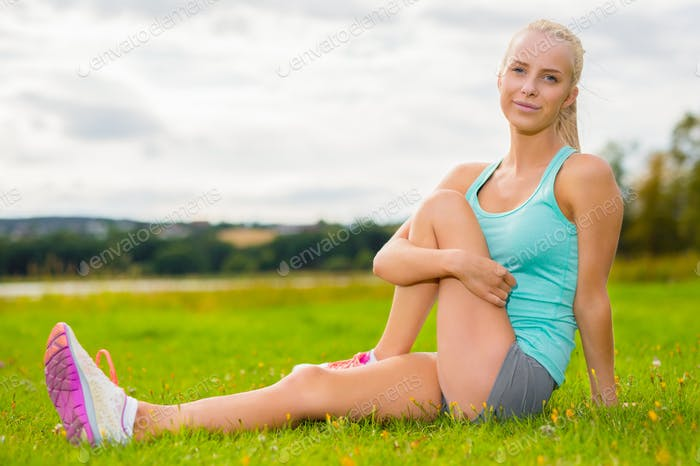 Fit blonde woman stretching outdoor on the grass
