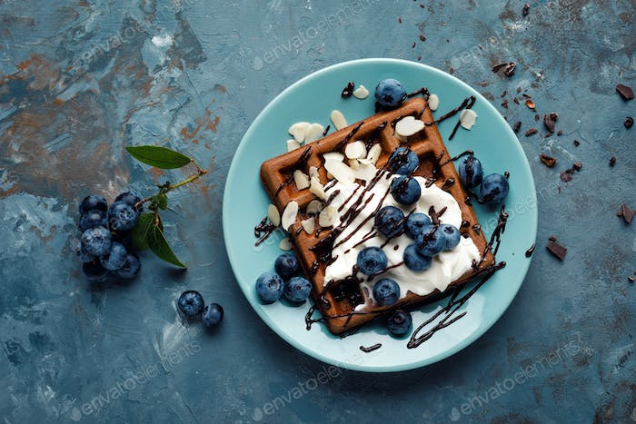Chocolate belgian waffles with ice cream and fresh blueberry on blue background, top view