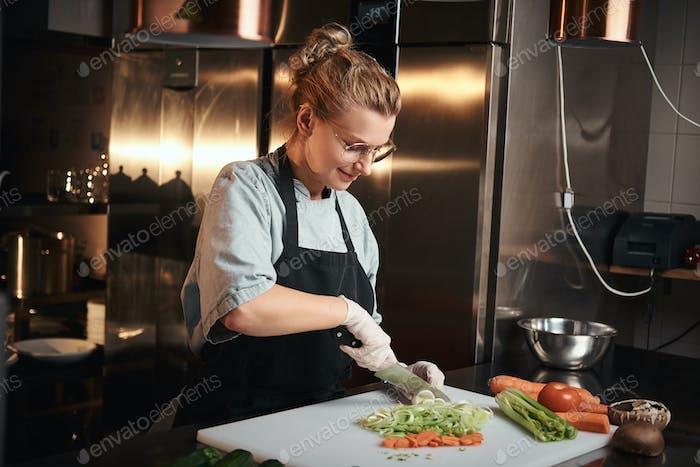 Europäische schöne weibliche Chefkoch in einer dunklen Restaurant-Küche