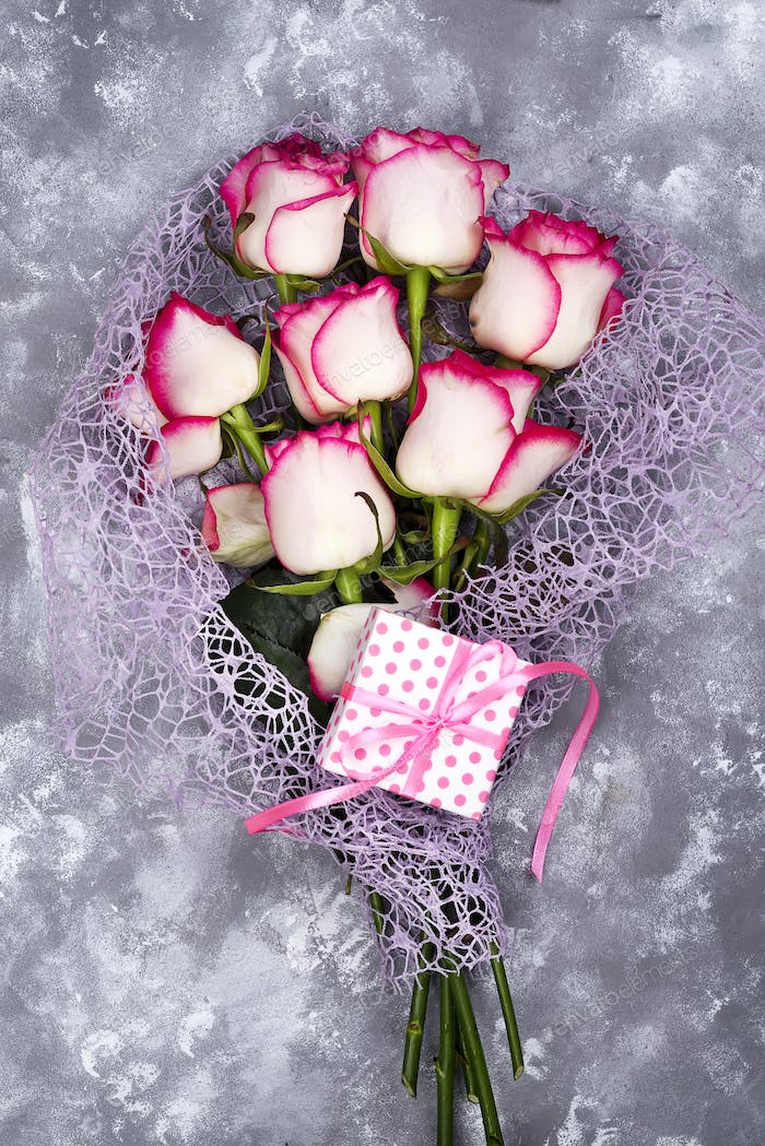 Red white rose flower bouquet with pink gift box on stone table.