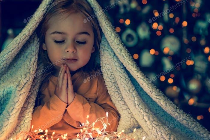 Pequeño bebé haciendo deseos de Navidad
