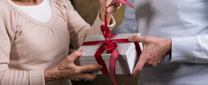 Man and woman holding gift