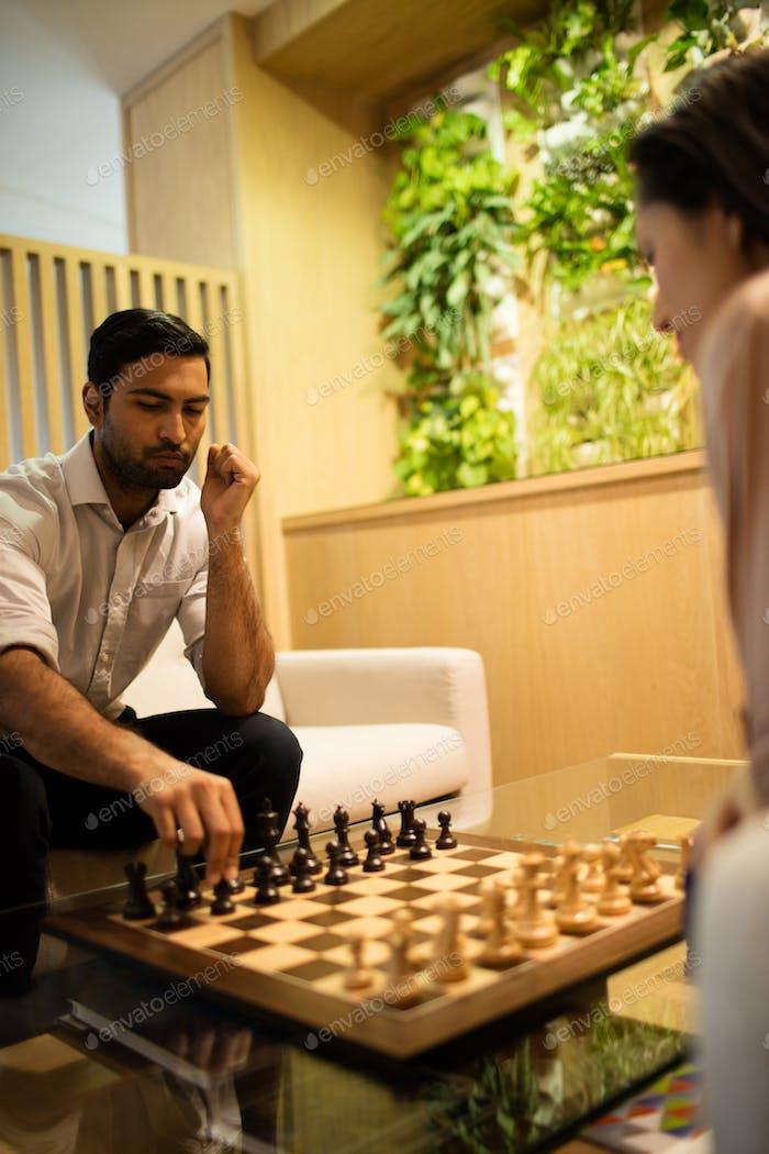 Geschäftsmann spielen Schach mit weiblicher Kollegin