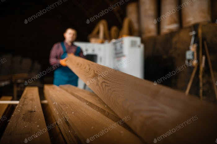Carpenter works on woodworking machine, lumber
