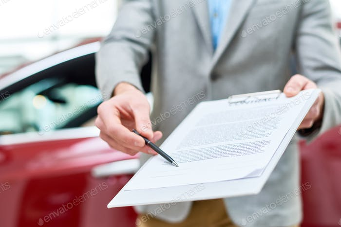Close Up Car Salesman Handing Contract to Client