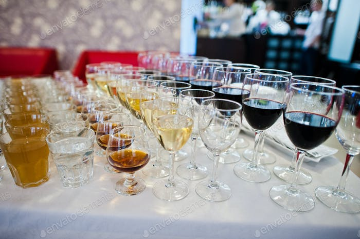 Different alcohol beverages in glasses on the table in restaurant or bar.