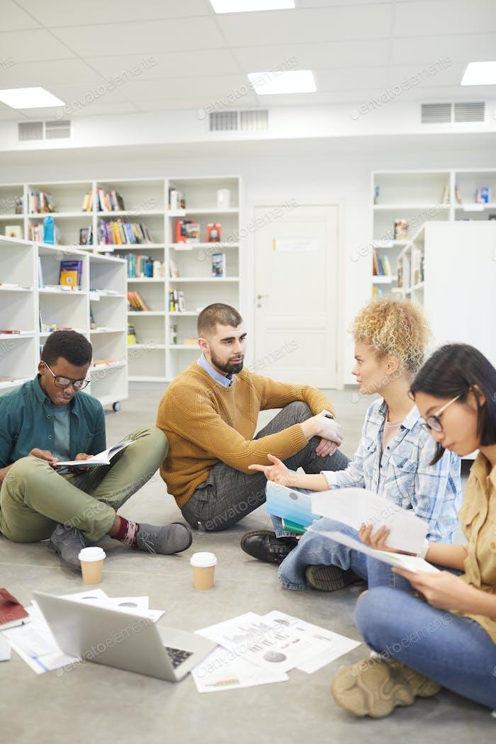 Junge Menschen studieren auf Boden in der Bibliothek