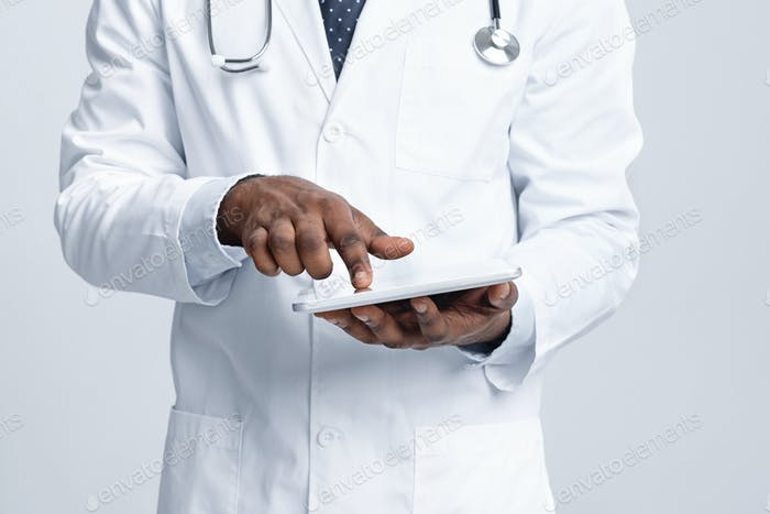 Cropped of african doctor using digital tablet