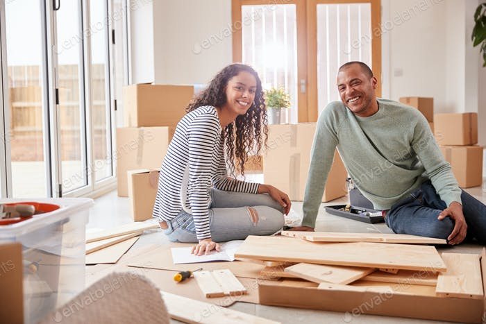 Portrait Of Couple In New Home On Moving Day Putting Together Self Assembly Furniture