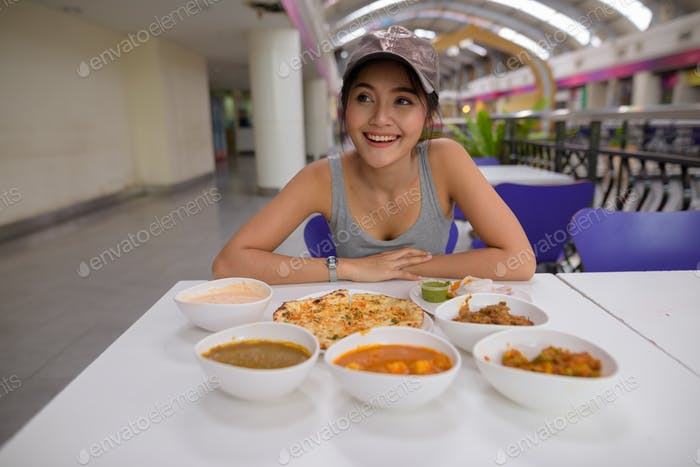 Young beautiful woman enjoying Indian food at restaurant