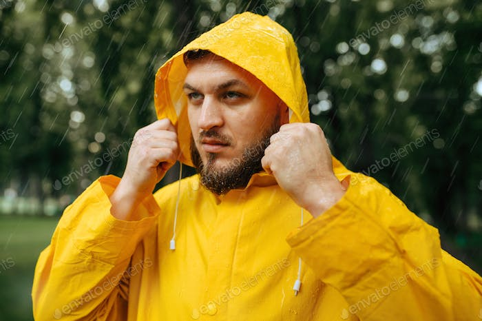 Man in raincoat puts on a hood in rainy day