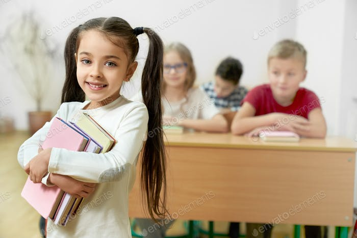 Charming student keeping several books in hands and posing