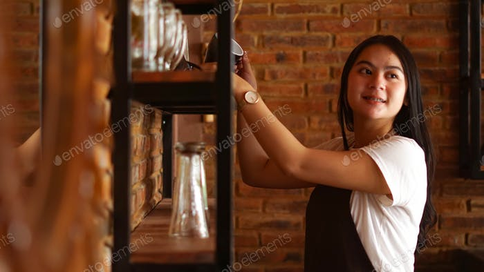 Asian Women Barista smiling and looking to camera. Barista female holding coffee cup at cafe