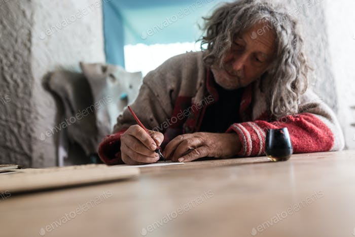 Elderly man doing calligraphy using a nib pen