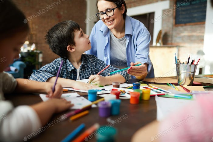 Female Art Teacher Working with Kids