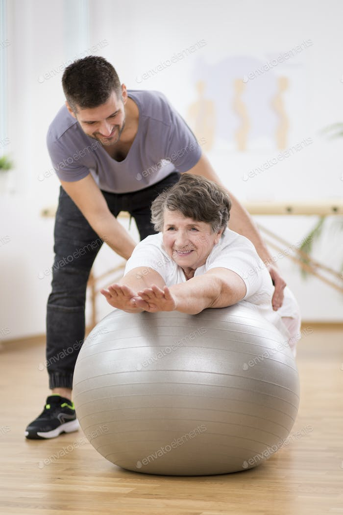 Thumbnail for Smiling physiotherapy student helping senior woman lay on the exercising ball during rehabilitation