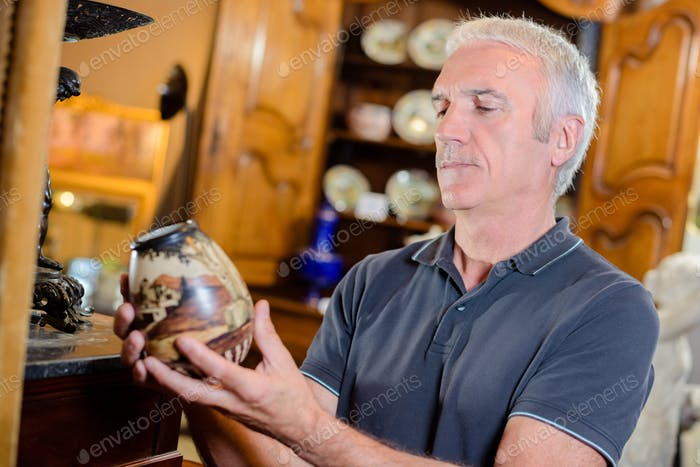 Man examining an antique pot