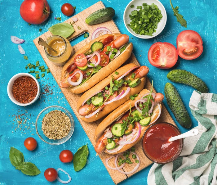 Homemade hot-dogs with fresh vegetables, spices, ketchup and mustard