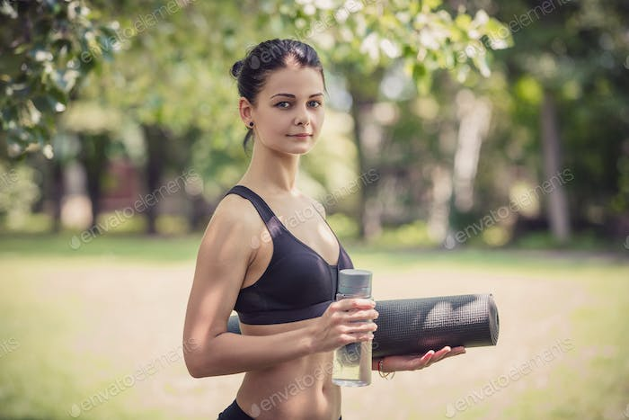 Young woman in sports clothing holding bottle of water and yoga mat