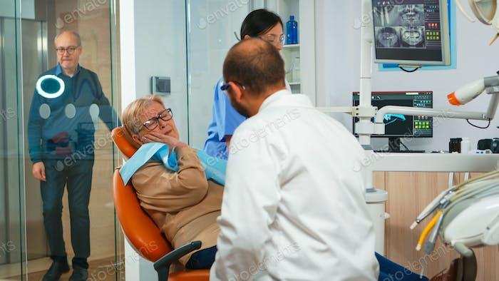 Frau mit Zahnschmerzen im Gespräch mit Kieferorthopädie