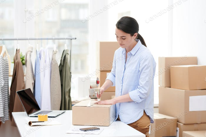 Young online shop manager with adhesive tape dispenser packing carton box