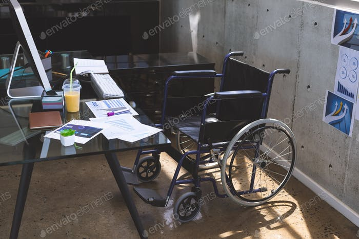 Empty wheelchair on a desk in the office