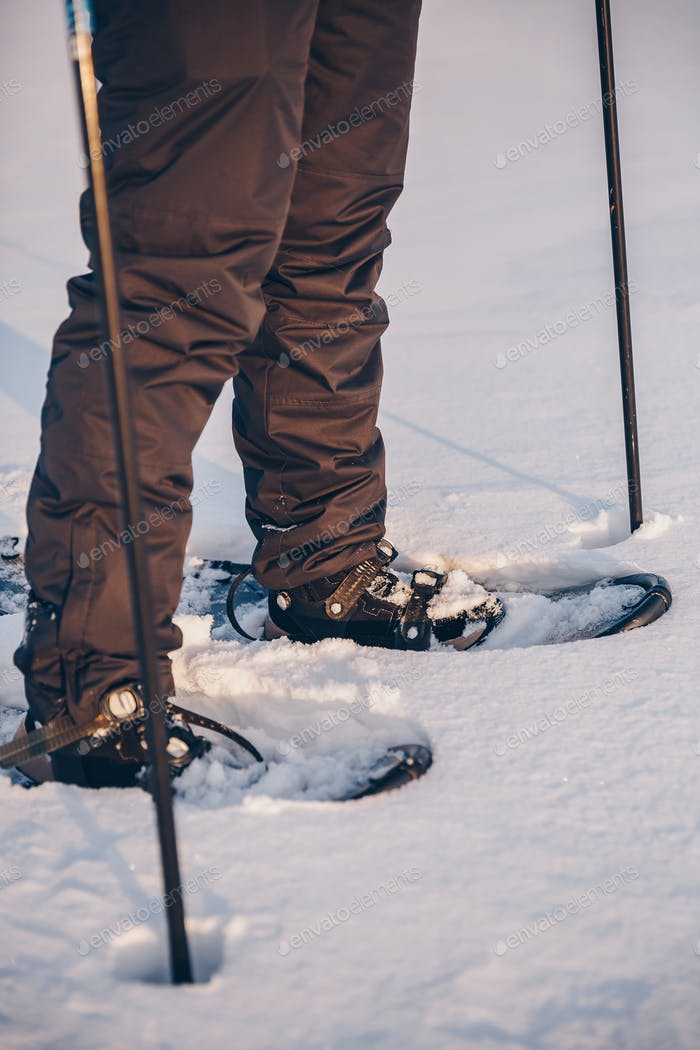 Man with snowshoe on the snow path close-up. Man in snowshoes with trekking poles in Finland