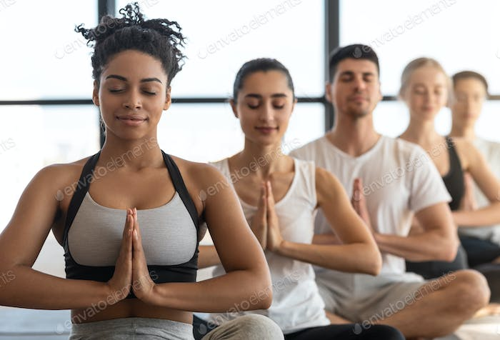 Yoga Class. Young Sporty Multicultural People Sitting In A Row, Meditating Together