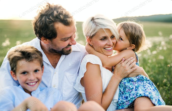 Young family with small children in summer nature at sunset.