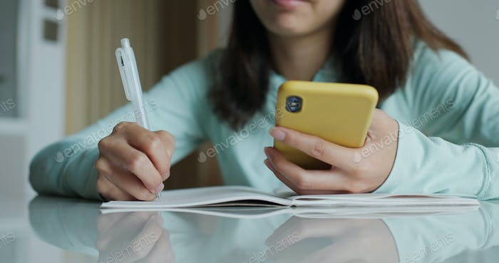Woman write on notebook with her cellphone at home