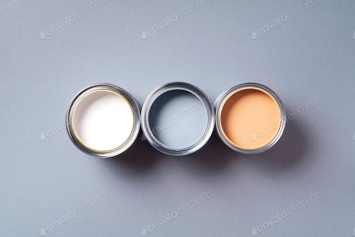 Open paint cans with on pastel background. Top view, copy space. Appartment renovation, repair