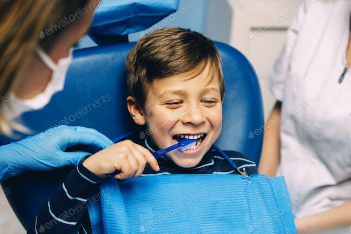 Arzt Zahnarzt lehrt ein Kind Zähne zu putzen.
