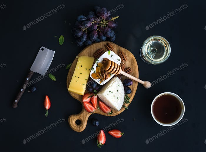 Cheese appetizer selection or whine snack set. Variety of cheese, grapes, pecan nuts