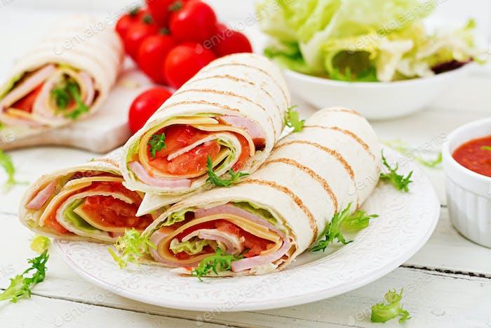 Tortilla Wrap mit Schinken, Käse und Tomaten auf weißem Holzhintergrund