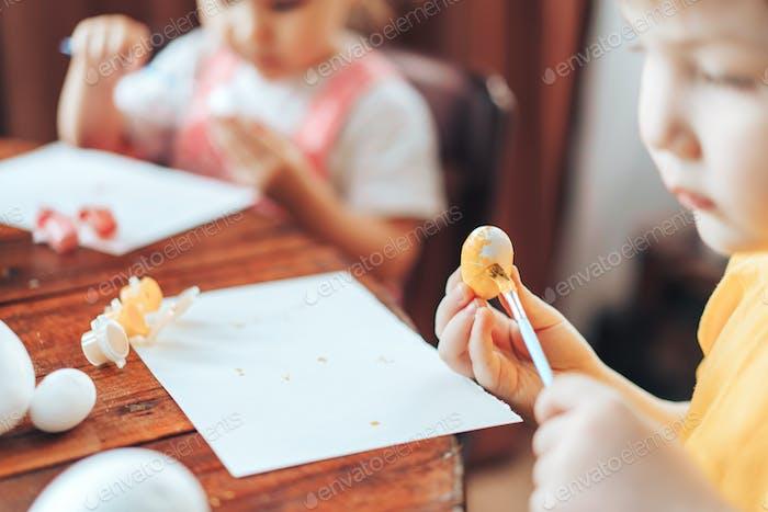 Kinder malen Ostereier für den Feiertag. Vorbereiten der Osterdekorationen für den Feier