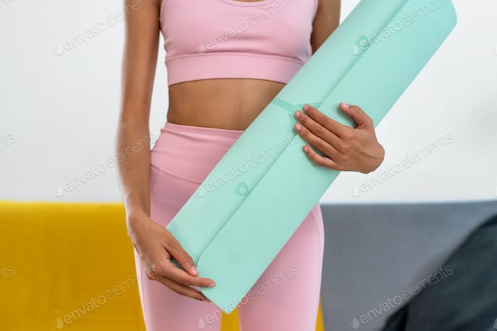 Cropped view of a woman holding a yoga mat after practicing at home