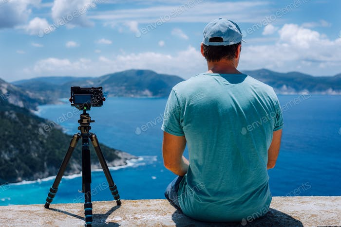 Travel Europe summer holiday in Greece. Happy man photographer enjoying cloudscape, coastline and