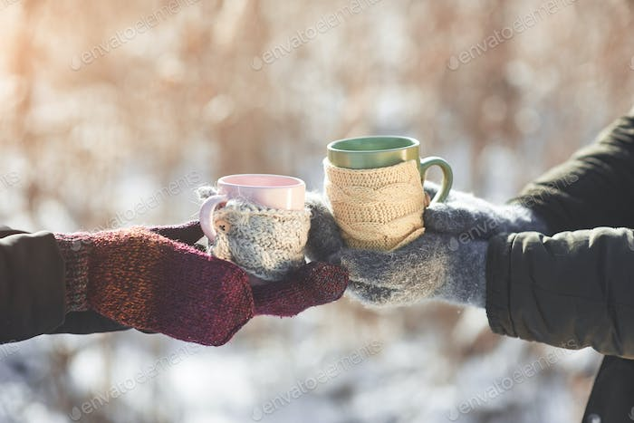 Couple hands in mittens take a mugs with hot tea in winter park