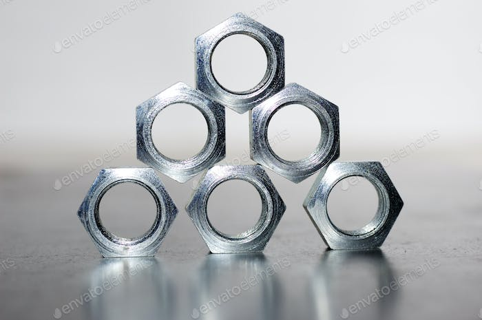 Close-up of a pyramid of five chrome metal nuts