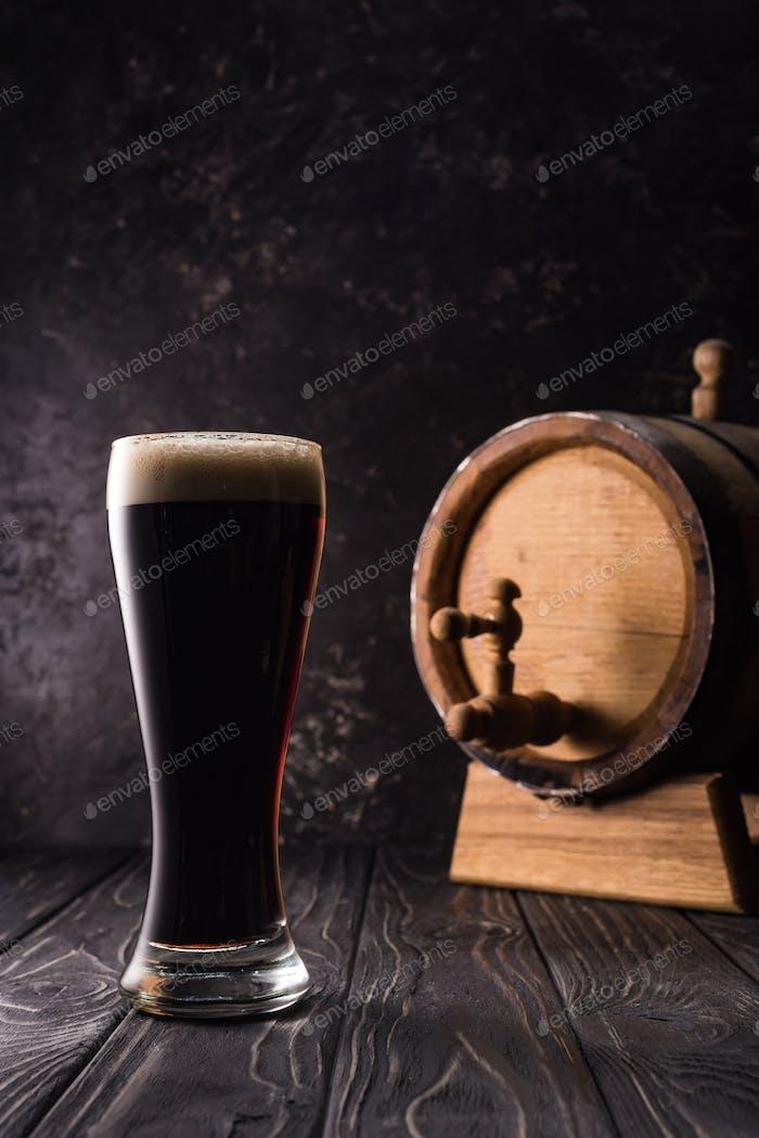 Glas Bier in der Nähe von kleinen braunen Fass mit Hahn auf Holztisch