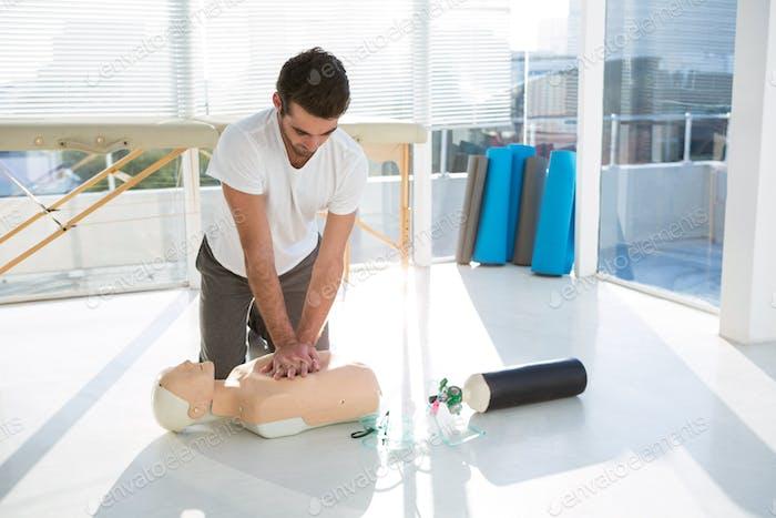 Paramedic practicing resuscitation on dummy