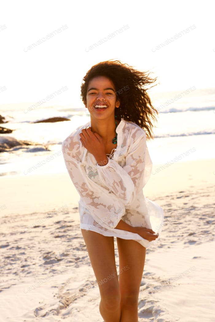 Fun young woman smiling on beach with summer dress