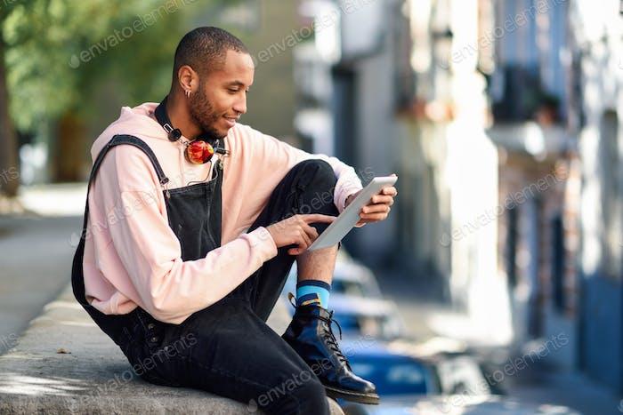 Junger schwarzer Mann mit digitalem Tablet im urbanen Hintergrund.
