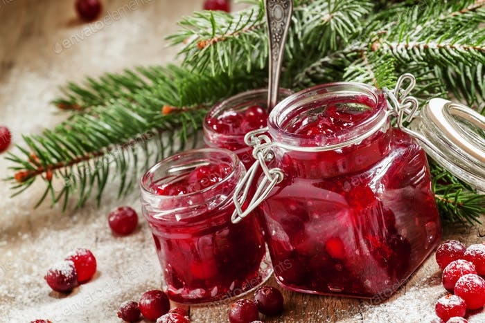 Winter cranberry sauce in glass jars with fresh cranberries, decorated fir branches