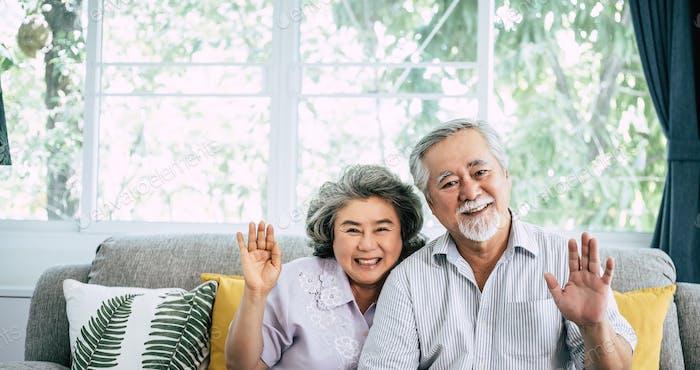 senior couple say Hi look at camera