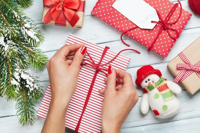 Weibliche Hände wickeln Weihnachtsgeschenk