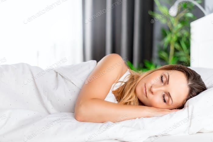 Красивая женщина мирно спит в постели утром