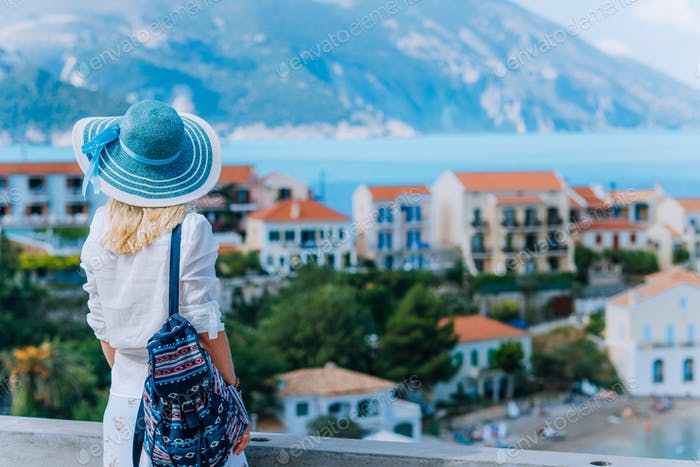 Young stylish traveler woman enjoying view of colorful tranquil Assos village. Female model wearing