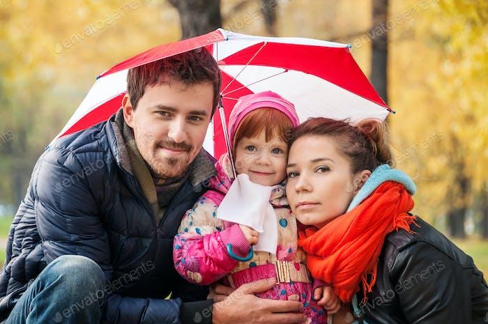 Familia joven Alegre bajo un paraguas en un Parque de otoño