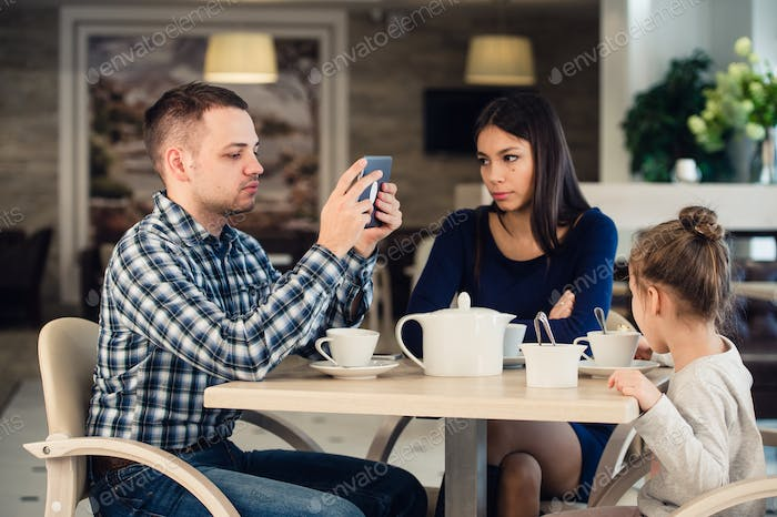 Modern family values. Father addicted about using electronic devices tablet pc, while his wife and